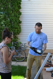 Finn shows Amanda how to crimp downspout